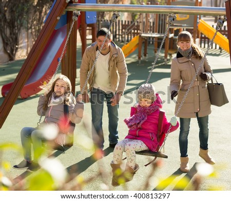 smiling american  family with two girls having fun on swings outdoors  - stock photo