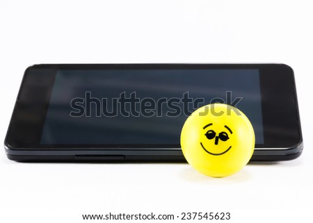 smiling and bouncing rubber ball near mobile phone - stock photo