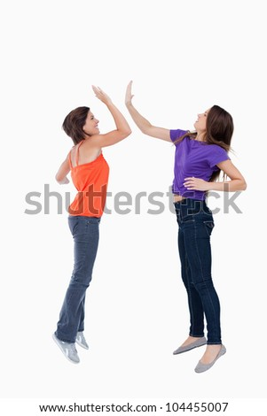 Smiling and dynamic teenagers jumping while giving a high-five - stock photo