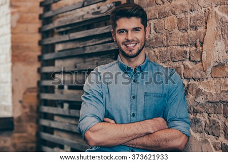 Smiling and handsome.Handsome young man keeping arms crossed and looking at camera with smile while standing against brick wall - stock photo