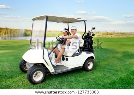 Smiling and happy couple driving a golf-cart with clubs on the back - stock photo
