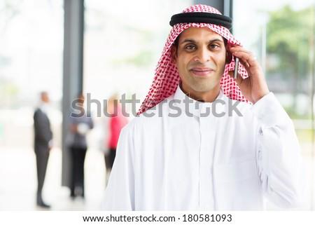 smiling arabian businessman talking on cell phone - stock photo