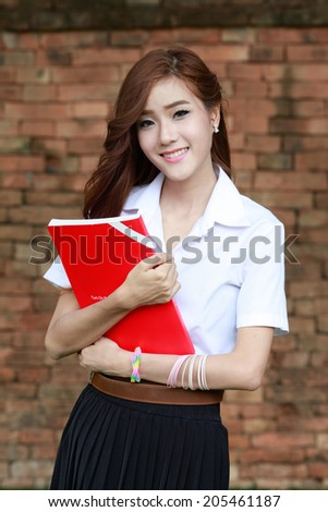smiling asian attractive college student woman in white uniform - stock photo