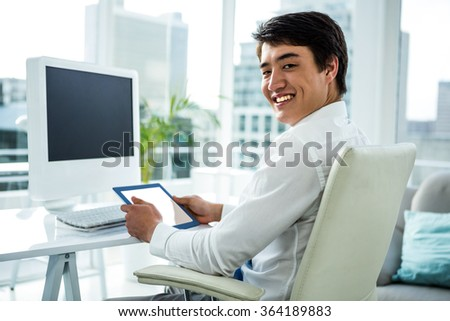 Smiling asian businessman using his tablet in his office - stock photo