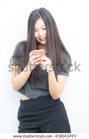 Smiling asian charming  woman is using on smartphone texting on white background. - stock photo