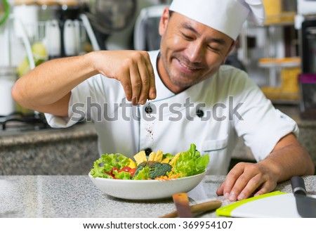 Smiling asian chef add spices in salad. Focus on hand and spice. - stock photo