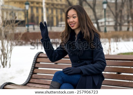 smiling Asian girl on a Park bench waving - stock photo