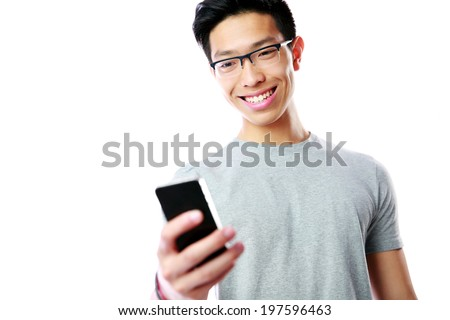 Smiling asian man using smartphone on gray background - stock photo
