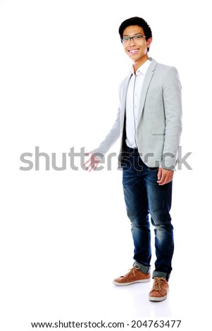 Smiling asian man with arm out in a welcoming gesture - stock photo