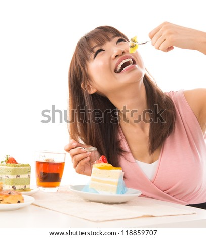 Smiling Asian woman eating cakes in the living room in her house - stock photo