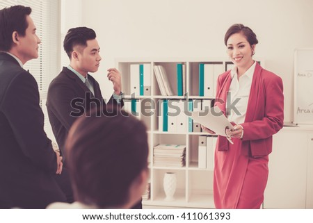 Smiling Asian woman explaining her idea to male business partners - stock photo
