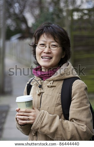 Smiling asian woman holds a coffee cup - stock photo