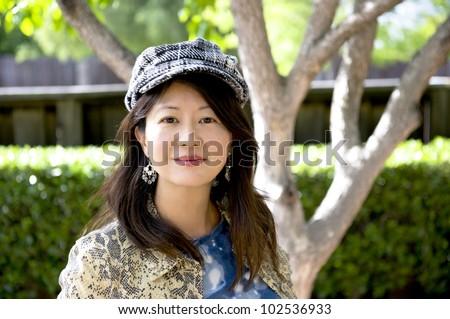 smiling asian woman with herringbone cap - stock photo