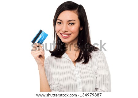 Smiling asian young female model holding up credit card. - stock photo
