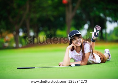 Smiling asian young woman laying on the green grass - stock photo