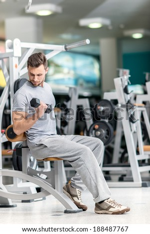 Smiling athlete bodybuilder man at biceps brachii muscles exercises with training dumbbells in fitness gym. Man looking on his arm - stock photo
