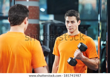 Smiling athlete man at biceps brachii muscles exercises with training dumbbells in fitness gym - stock photo