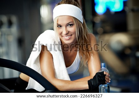 Smiling athletic woman resting on a treadmill - stock photo
