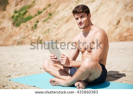 Smiling athletic young man sitting and using tablet on the beach - stock photo