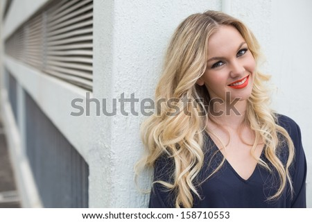 Smiling attractive blonde wearing classy dress outdoors against building - stock photo