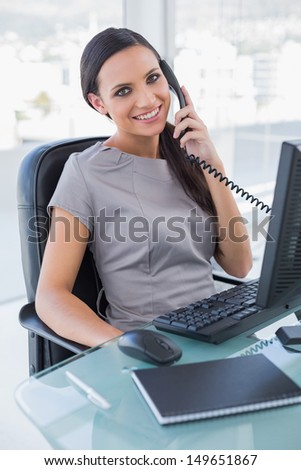 Smiling attractive businesswoman answering phone in her office - stock photo