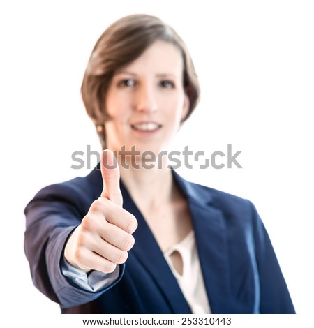 Smiling attractive businesswoman giving a thumbs up of approval and success isolated over white. - stock photo