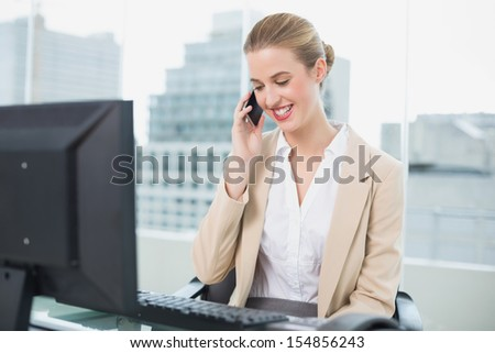 Smiling attractive businesswoman on the phone in bright office - stock photo