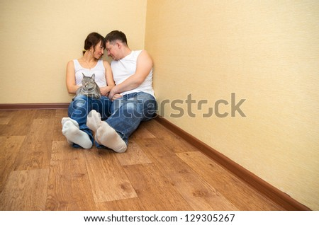 Smiling attractive couple sitting on floor in home - stock photo