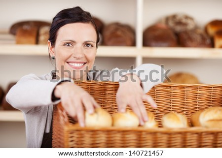 Smiling attractive female assistant selecting rolls in a bakery from a large wicker basket and smiling at the camera - stock photo