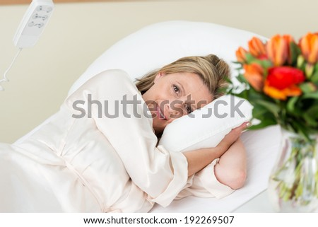 Smiling attractive female patient lying in a hospital bed cuddling down into the pillows as she smiles bravely at the camera, view past roses on the side table - stock photo