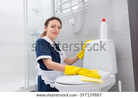 Smiling attractive housekeeper or housewife wearing a neat white apron kneeling down cleaning a toilet cover with a yellow cloth in a clean white bathroom - stock photo