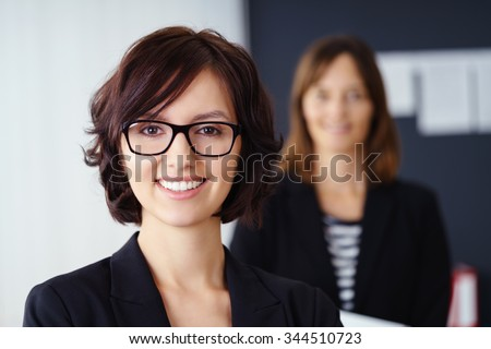 Smiling attractive manageress or team leader posing in the foreground with a team member or co-worker visible in the background as a blur, head and shoulders portrait - stock photo