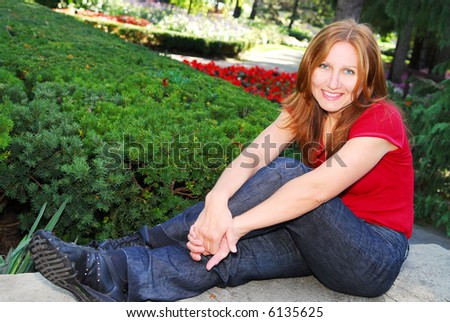 Smiling attractive mature woman relaxing in summer park - stock photo