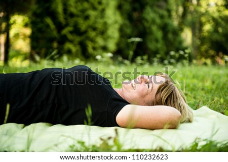 Smiling attractive senior woman lying outdoor on rug in nature - stock photo