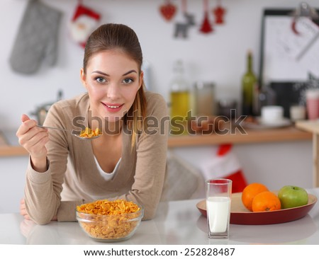 Smiling attractive woman having breakfast in kitchen interior - stock photo