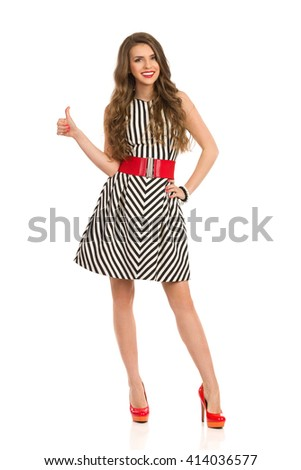 Smiling attractive woman in black and white striped dress and high heels posing with hand on hip, looking at camera and showing thumb up, Full length studio shot isolated on white. - stock photo