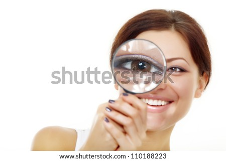 Smiling attractive woman looking through a magnifying glass over white background - stock photo