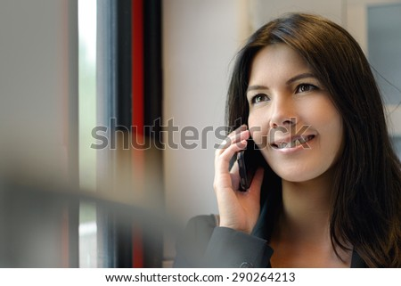 Smiling attractive woman talking on her cell phone while riding in a train or bus, commuting from work - stock photo