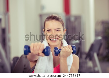Smiling attractive woman working out with dumbbells raising and extending her arms to tone and strengthen her muscles, close up head and shoulders looking at camera - stock photo