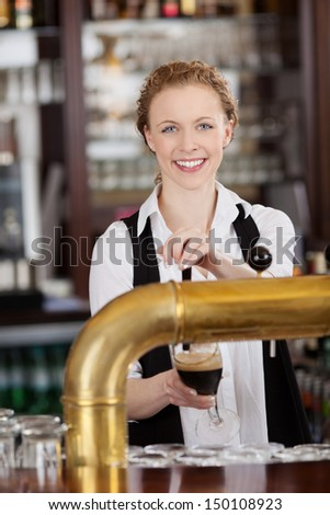 Smiling attractive young barmaid standing behind the bar serving dark draft beer - stock photo