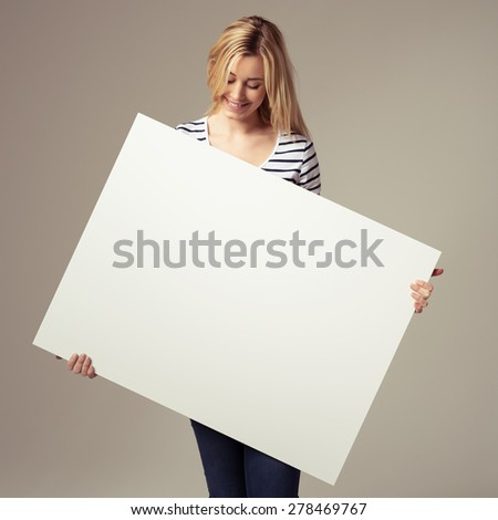 Smiling attractive young blond woman holding a blank white sign with copyspace at an angle in her hands looking down at it with a smile, over grey - stock photo