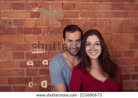 Smiling attractive young couple posing in front of a brick wall in an affectionate embrace looking at the camera with friendly smiles - stock photo