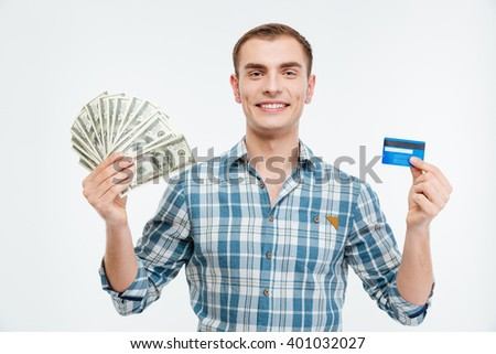 Smiling attractive young man holding cash and credit card over white background  - stock photo