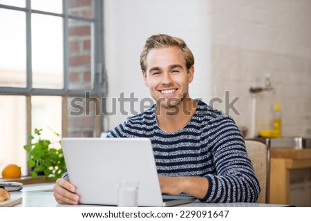 Smiling attractive young man with a beaming smile working on his laptop at home in the kitchen of his apartment - stock photo