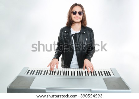 Smiling attractive young man with long hair in sunglasses playing on synthesizer over white background - stock photo