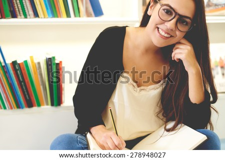 Smiling attractive young student wearing glasses sitting cross legged studying on the floor in front of a bookcase full of books - stock photo