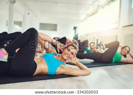 Smiling attractive young woman doing aerobics in the gym with a group of young women in a health and fitness concept - stock photo