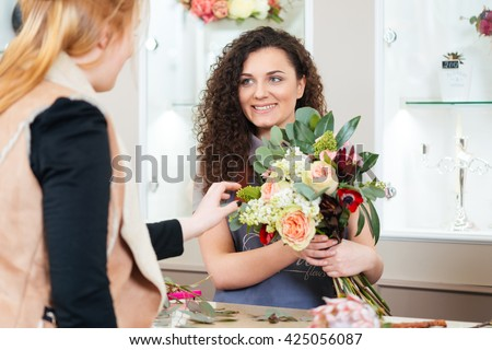 Smiling attractive young woman florist showing bouquet of flowers to customer - stock photo