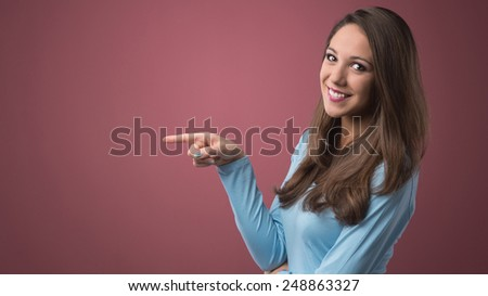 Smiling attractive young woman pointing left and looking at camera - stock photo
