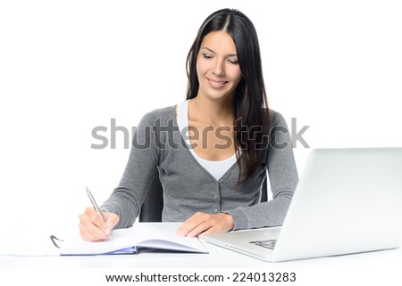 Smiling attractive young woman working at a desk with her laptop computer writing notes in a notebook conceptual of a hardworking office worker or businesswoman, or a student studying by e-learning - stock photo
